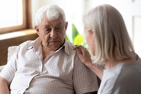 Worrying middle aged woman comforting upset older man, sitting together on couch at home. Mature sensitive wife soothing elder unhappy husband, showing love, giving support and psychological help.