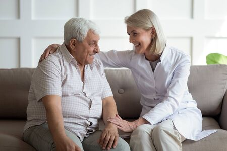 Friendly mature general practitioner communicating with pleasant 80s male patient, sitting together on sofa. Smiling trustful middle aged doctor giving psychological help to elder man at home visit.