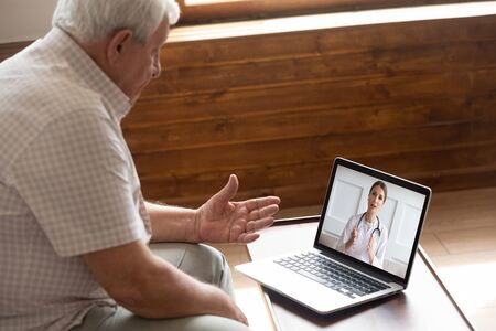 Focused older 80s male patient consulting with doctor via computer video call. Senior man looking at laptop screen, talking to therapist cardiologist online, older generation using modern technology.