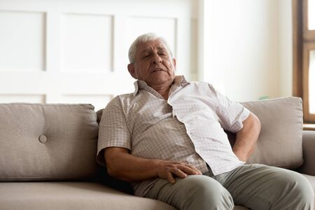 Unhealthy older man leaning on couch, suffering from strong pain in back. Unhappy elder grandfather feeling unwell, waiting for ambulance aid, resting alone on sofa at home, reducing painful feelings.