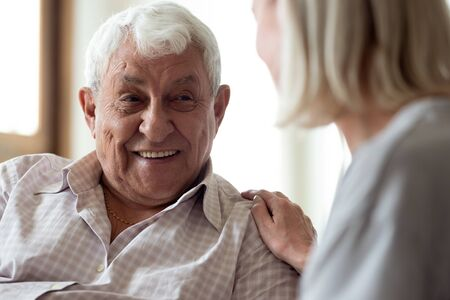 Happy older man feeling relieved after talking to supporting middle aged wife. Smiling elder male patient communicating with nurse. Female medical worker showing professional care and understanding.