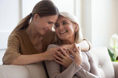 Colpo di testa giovane donna adulta felice che abbraccia mamma anziana sorridente seduta sul divano. Gioiosa famiglia femminile di due persone che si rilassano, parlano, comunicano sul divano di casa, godendosi un dolce momento tenero insieme.