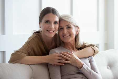 Head shot close up portrait smiling young woman embracing from back sitting on couch middle aged mother. Happy two generations retired mom and grown up daughter posing for photo in living room.