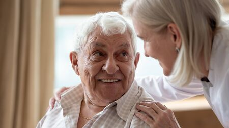 Head shot close up cheerful elderly man looking at pleasant middle aged nurse. Mature female doctor embracing shoulders, communicating with smiling 80s patient, giving support and psychological help.