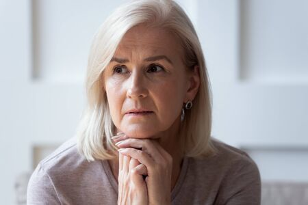 Head shot close up portrait thoughtful middle aged retired woman worrying about personal health problems. Upset older female retiree thinking of family troubles, feeling lonely, sitting at home. Stockfoto