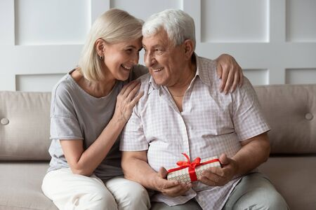 Happy older 70s man feeling thankful to smiling attractive mature wife for prepared wrapped gift. Joyful middle aged woman congratulating sincere husband with birthday or marriage anniversary.