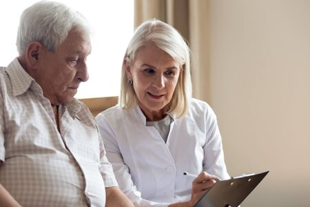 Pleasant middle aged female doctor general practitioner holding clipboard, explaining medicine prescription or diagnosis details to attentive older male patient, sitting together on couch, head shot.