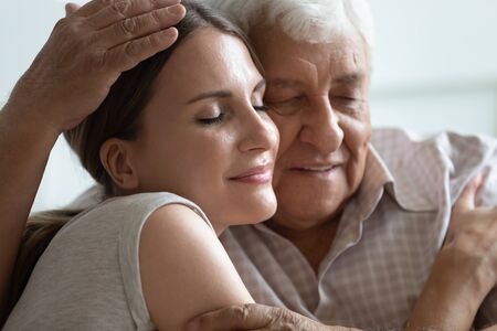 Close up head shot caring older hoary man hugging loving grown up daughter at home. Young pleasant attractive woman snuggling to 80s father, enjoying sweet bonding family moment together at home.