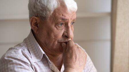 Close up colpo di testa premuroso infelice uomo anziano guardando fuori dalla finestra, pensando a problemi di salute. Pensionato pensieroso degli anni '80 che manca di figli cresciuti, aspetta la visita dei nipoti, si sente solo.