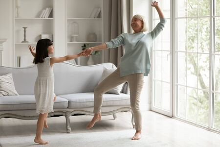 Full length view in modern light cozy living room having fun different age generation women, 60s grandmother hold hand little active granddaughter dancing enjoy life at active weekend at home concept Stockfoto