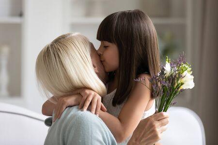 Sincère petite-fille mignonne fort câlins et embrassant dans la joue sa grand-mère des années 60 lui a donné de jolies fleurs printanières félicitations avec anniversaire, journée internationale de la femme, gros plan image concept