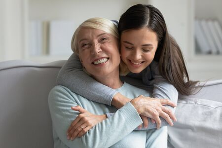 Grown up daughter strong cuddle loving 60s mother close up view, different generations women spend time in living room enjoy moment of caress and closeness having warm relation, giving support concept