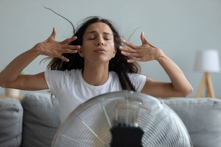 Woman seated on couch in living room suffers from swelter waving her hands trying to cool off by the fan, oppressive heat too hot weather and sultriness in summer, flat without air-conditioner concept