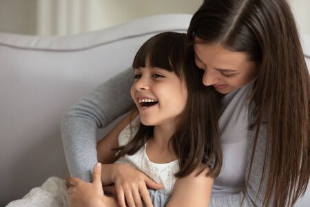 Close up pretty little daughter having fun at home with loving caring mother, people resting on couch joking feels happy. Older sister spend time with younger tickles her, enjoy communication concept