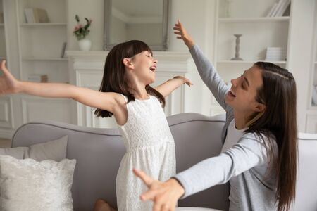Cheerful little daughter stretching raised hands rush to get into moms hugs people missed each other. Younger and older sister playing spend time at home laughing enjoy funny weekend together concept