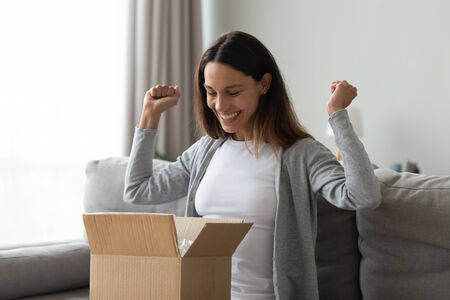 Cheery woman sitting on couch opening cardboard box feeling excitement and happiness girl received long-awaited carton package, fast post mail parcel delivery, reliable postal courier service concept