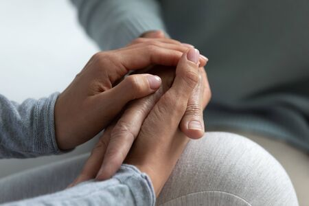 Close up of grown up daughter holding hand of mother, shares all hardship and illness of dear person, concept of express care, giving psychological support, trust empathy and understanding in family Stock Photo