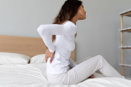 Side view 30s woman in nightclothes touches or massages back while awake get out of bed feels discomfort painful feelings in lower back caused by poor sleeping position, sign of bad mattress concept 版權商用圖片