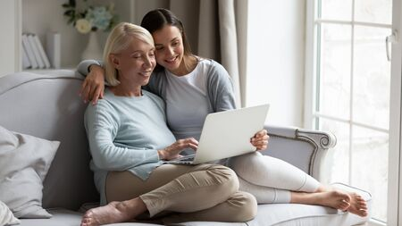 Elderly 50s mother grown up daughter resting on couch in living room holding on lap computer look at screen watching movie film, using device for videocall, shopping through e-commerce website concept