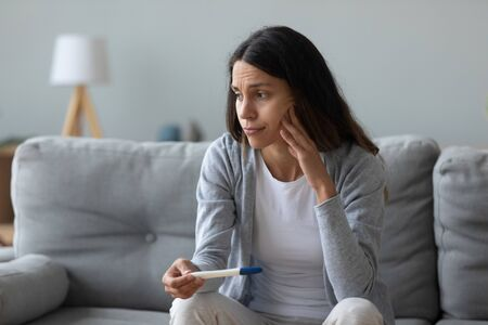 Woman sitting on couch feels frustrated about positive test and unplanned pregnancy. 30s female lost in sad thoughts has difficulties getting pregnant, infertility, feminine health problems concept