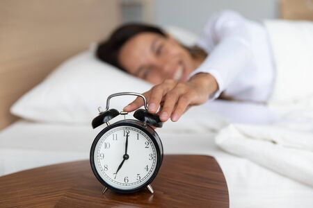 Woman woke up at seven oclock, close up focus to female extend hand turns off wind-up alarm clock on bedside table. Concept of enough healthy sleep, good morning, beginning of happy new wonderful day