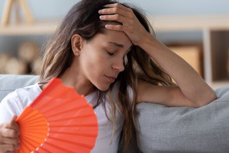 Close up view millennial woman sitting on couch exhausted by hot weather closed eyes feels unwell dying of heat holding in hand orange fan using it for reducing too hot temperature indoors concept Standard-Bild