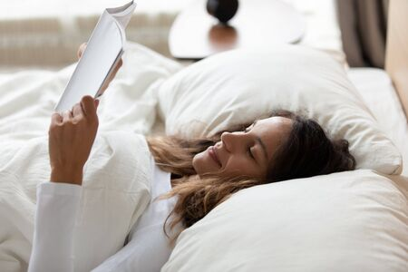 Close up of woman awakened lies in bed hold educational material learns information at test day, book lover read next chapter in morning, start new day with hobby, enjoy weekend and pastime concept