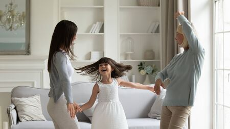 Elderly 50s grandmother her grown up daughter and granddaughter fool around spend weekend together standing in modern living room dancing moving enjoy life, funny activities having fun at home concept