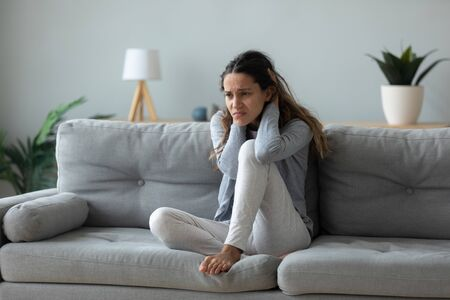 Unhappy young woman sitting on couch lost in sad thoughts goes through divorce separation with husband or break up, personal life problems, addicted person need alcohol or drug rehab treatment concept
