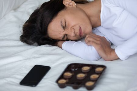 Close up depressed woman lying on bed near cellular and sweets suffers from divorce, break up with boyfriend wait for call crying regretting about fight, psychological emotional mental stress concept