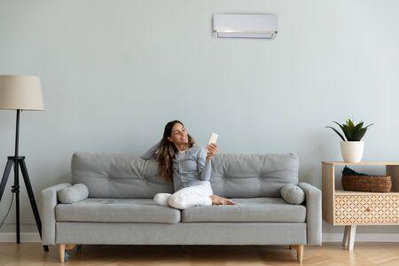Kobieta spędza czas w domu siedząc na kanapie trzymając pilota steruje stopniami używa klimatyzatora ciesz się klimatyzowanym nowoczesnym mieszkaniem, obniża ciepło lub zimno do komfortowej temperatury