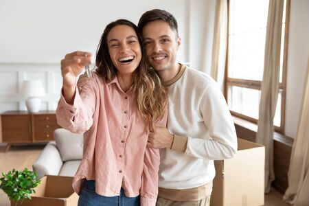 Happy young family couple holding key to new home on moving day concept, first time real estate owners man husband embrace woman wife look at camera proud buying property stand in own flat with boxes