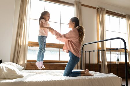 Cute active little kid girl jumping on bed flying in air playing with mum, happy parent young mother having fun with funny small child daughter laughing enjoying leisure morning together in bedroom Stockfoto