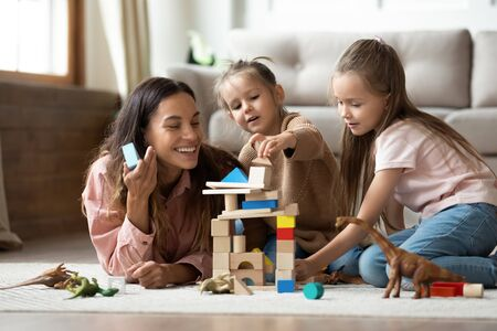 Happy young mum babysitter helping playing game with little kids daughters on floor, female nanny mother and cute small children sisters building castle of wooden blocks having fun with toys at home