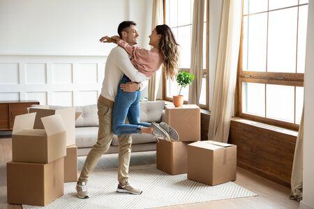Glücklicher junger Ehemann, der aufgeregte Frau hebt, die den Umzugstag mit Pappkartons feiert, stolzes überglückliches Familienpaar, das zum ersten Mal Hauskäufer Mieter Besitzer, die Spaß haben, genießen Umzug, Hypothekenkonzept Standard-Bild