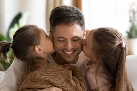 Cute little kids daughters kissing happy young dad on cheeks congratulating with fathers day, smiling daddy and two small children girls bonding cuddling enjoying sweet tender moment of love concept