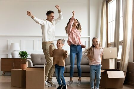 Funny happy family young parents and cute little kids children daughters dancing in living room jump together having fun celebrating moving day relocating in new home renovating apartment with boxes Stockfoto - 134273720