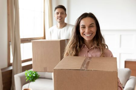 Smiling young wife holding cardboard box relocating into new home with husband looking at camera packing, happy couple first time real estate buyers renters owners tenants buy rent house concept