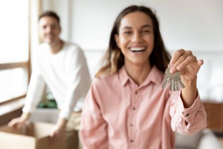 Happy young wife hold keys to new home relocate with husband and boxes into own flat, family couple first time property buyers renters owners tenants buy rent house, mortgage, moving day concept