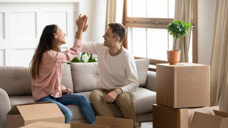 Glückliches stolzes tausendjähriges Paar gibt High Five und feiert die Erreichung des Familienziels beim Einzug in ein neues Zuhause, junge Familienmitbewohner, Mieter, Mieter, Eigentümer, sitzen auf dem Sofa mit Kisten ziehen in ein eigenes Hauskonzept um