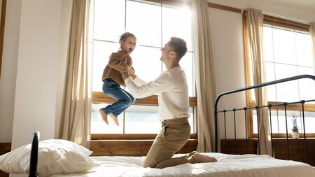 Funny cute kid daughter laughing jumping on bed playing with dad in bedroom interior, happy father holding lifting small child girl flying in single daddy arms enjoying family morning life having fun