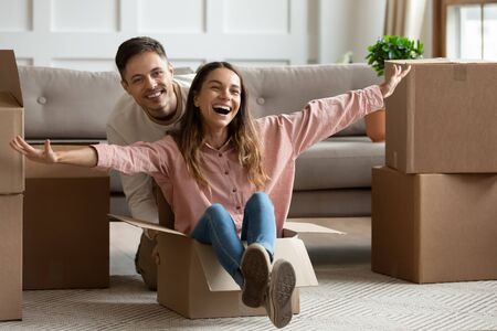 Happy overjoyed young family couple first time home buyers owners having fun unpacking riding in box on moving day, funny husband and wife packing in new house apartment celebrate relocation concept