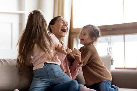 Cheerful positive family cute small funny kids children daughters enjoying tickling playing lifestyle game with young happy mum embracing laughing having fun relaxing sitting on sofa at home together