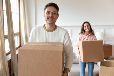 Happy young man carrying box moving into new house with girlfriend, smiling couple roommates renters tenants packing unpacking relocating removals standing in modern rental apartment new home concept