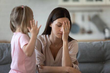 Müde alleinerziehende Mutter fühlen sich verzweifelt gestresst, weil sie hartnäckige Kindertochter-Wutanfälle schreien, frustrierte depressive junge erwachsene Mutter, die von frechen schwierigen rebellischen Kindermädchenproblemen genervt ist Standard-Bild