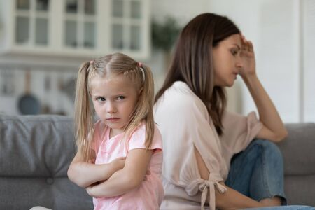 Naughty stubborn little child daughter and worried mum avoid talk after argument sit turn back on sofa, fussy preschool kid girl sulking ignore mother at home, parents with children conflicts concept