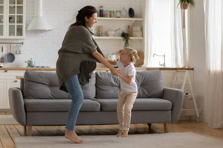Excited young adult mom and kid daughter hold hands laughing dancing together in modern kitchen interior, happy active joyful family mum and cute small child girl jumping having fun bonding at home Stockfoto - 134273863