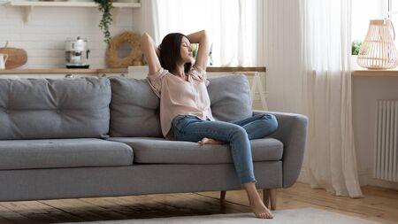 Spokojna pani domu gospodyni siedzi na kanapie czuć zmęczenie drzemiący trzymać ręce za głową, spokojna młoda kobieta odpoczywać na wygodnej kanapie z zamkniętymi oczami świeże powietrze w przytulnym czystym nowoczesnym salonie w domu