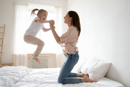 Cheerful mum babysitter play with cute active small kid girl jump on bed, happy carefree mother and little child daughter holding hands laughing having fun feel joy at home in modern bedroom interior Stockfoto - 134273897