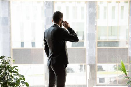 Back view of busy successful businessman in official suit stand near big office window look in distance talking on cellphone, confident man employee speak on smartphone use fast internet connection